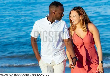Close Up Portrait Of Young Diverse Couple In Casual Wear Holding Hands On Beach. African Man And Cau