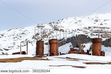 Abandoned marble mining machinery at Camp Mansfield, New London, Svalbard. Snow covered mountain background with blue sky.