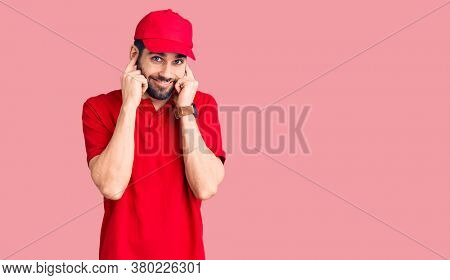Young handsome man with beard wearing delivery uniform covering ears with fingers with annoyed expression for the noise of loud music. deaf concept.