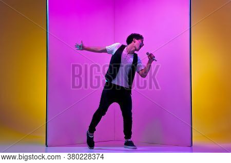 Celebrity. Young Male Musician, Singer Performing On Pink-orange Background In Neon Light. Concept O