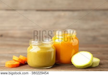 Glass Jars With Nutrient Baby Food On Grey Wooden Background. Vegetable And Fruit Puree