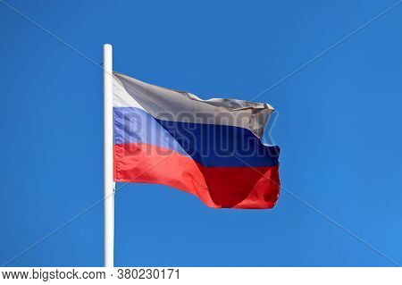 Russian Flag Waving Against The Clear Blue Sky. Symbol Of Russia, Russian Authority Concept