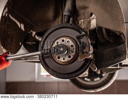 Auto Car Repair Service Center. Mechanic Checking Wheel Bearings In Car Workshop