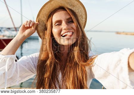 Image of cheerful ginger woman showing tongue and taking selfie photo while walking on promenade