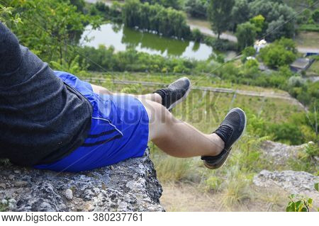 A Man Sits On The Edge Of A Cliff, And His Legs Hang From A Cliff