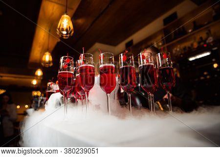 Glasses With A Red Drink Are On The Bar.the Glass Is Decorated With Cherries. Glasses Are Surrounded