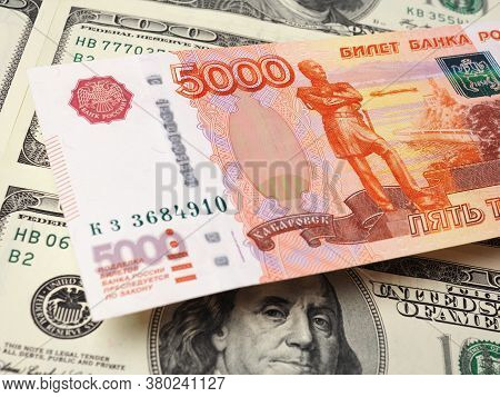 A Russian Five-thousand-ruble Bill Hangs Over A Field Of American Hundred-dollar Banknotes