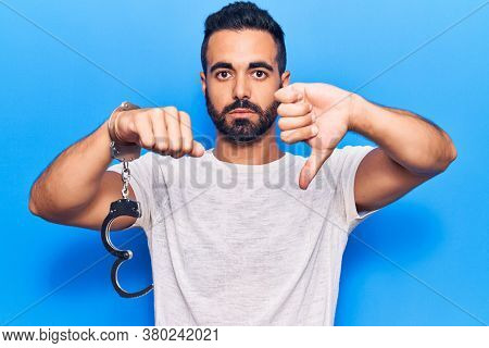 Young hispanic man holding prisoner handcuffs with angry face, negative sign showing dislike with thumbs down, rejection concept
