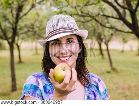 Beautiful Woman Smiling In Nature. Happy People Lifestyle. Woman Smiling In Orchard With Apple. Natu