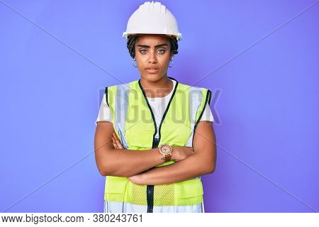 Young african american woman with braids wearing safety helmet and reflective jacket skeptic and nervous, disapproving expression on face with crossed arms. negative person.