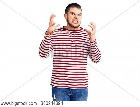 Young handsome man wearing striped sweater shouting frustrated with rage, hands trying to strangle, yelling mad