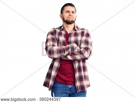 Young handsome man wearing casual shirt skeptic and nervous, disapproving expression on face with crossed arms. negative person.