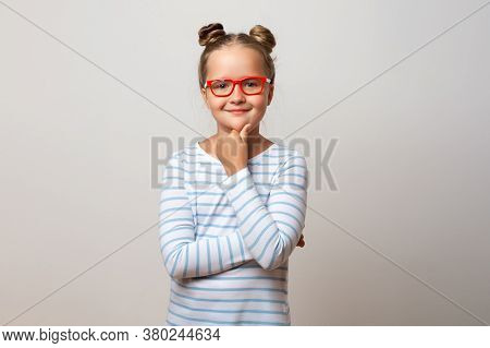 Portrait Of A Pensive Thinking Little Schoolgirl Girl In Glasses On A White Background. Child Holdin
