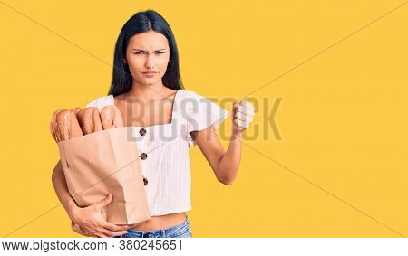 Young beautiful latin girl holding paper bag with bread annoyed and frustrated shouting with anger, yelling crazy with anger and hand raised