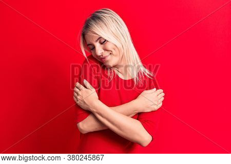 Young beautiful blonde woman wearing casual red t-shirt standing over isolated background hugging oneself happy and positive, smiling confident. Self love and self care