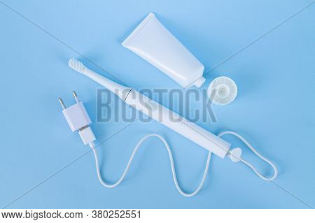 Rechargeable Sonic Or Electric Toothbrush Set With Charger And Toothpaste On Blue Background Top Vie
