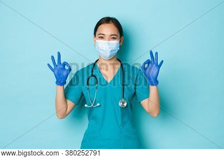 Covid-19, Social Distancing And Coronavirus Pandemic Concept. Satisfied Smiling Asian Female Doctor,