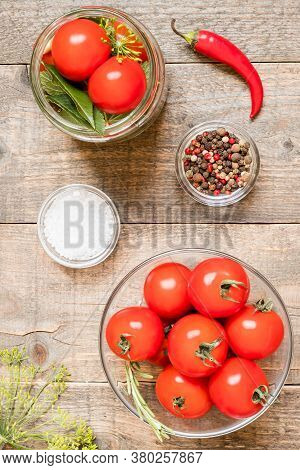Top View Jar With Canned Tomatoes And Seasonings On Wooden Kitchen Table. Food Preservation And Cons