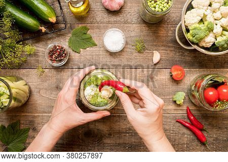 Hand Add Red Hot Peppers While Canning Broccoli And Cauliflower To Glass Jar And Other Canning Veget