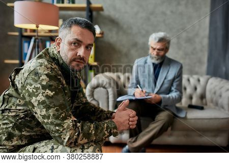 Middle Aged Military Man Looking Aside During Therapy Session With Psychologist. Soldier Suffering F