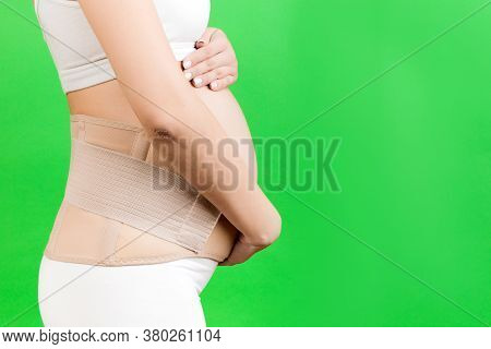 Side View Of Pregnant Woman In Underwear Wearing Pregnancy Belt At Green Background With Copy Space.