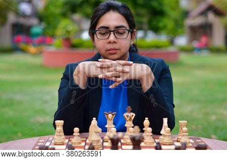 An Indian Girl Playing Chess Waiting For The Opponent To Play And Anxiously Thinking About Her Next