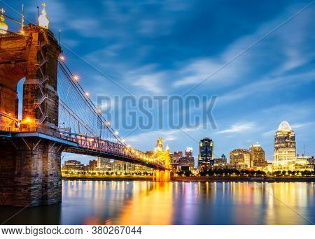 Nighttime view of John A. Roebling Suspension Bridge over the Ohio River and downtown Cincinnati skyline