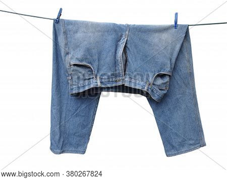 Wet Wrinkled Blue Shabby Jeans Hanging On A Wire On Two Clothespins For Drying Outdoors. Washing Clo