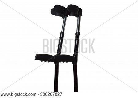 Two Crutches Of Dark Color On A White Background. A Pair Of Adjustable Crutches With Support Under T