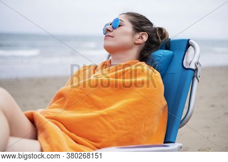 Woman Relaxing In A Beach Chair In Front Of The Ocean In Summertime
