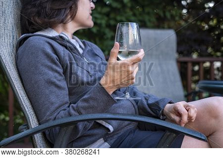 Woman Drinking A Glass Of White Wine On Her Backyard Deck