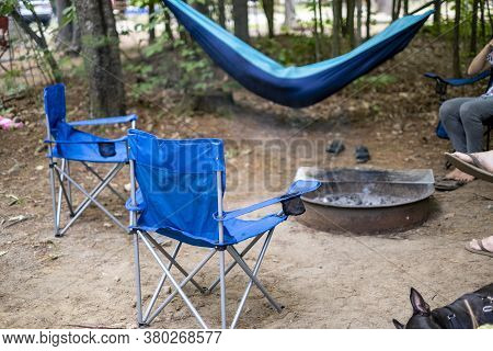 Folding Chairs Around A Campfire.  Camping In The Woods With A Fire Pit.
