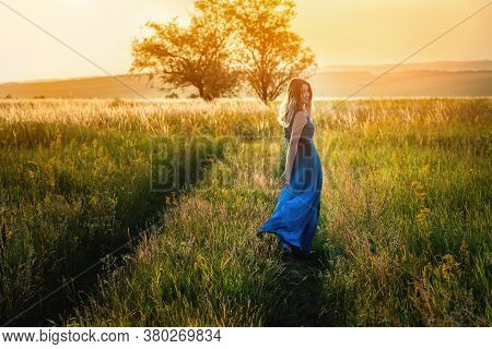 A Beautiful Blonde Woman In A Blue Dress Walks Along The Field At Sunset. The Concept Of Beauty, Fre