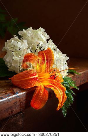 Hydrangea And Daylily On A Wooden Table. Day-lily And White Hydrangea On A Dark Background. Still Li