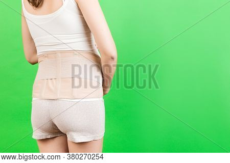 Back View Of Pregnant Woman Wearing Pregnancy Belt At Green Background With Copy Space. Close Up Of