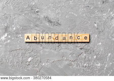 Abundance Word Written On Wood Block. Abundance Text On Table, Concept