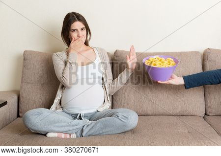 Pregnant Woman Sitting On The Sofa Refuses To Eat Unhealthy Snacks. Stop To The Junk Food During Pre
