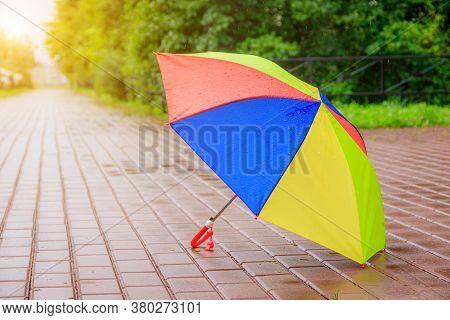 An Open Colored Umbrella Stands On The Asphalt. Summer Rain. Article About Choosing An Umbrella. Chi