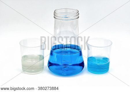 One Flask With Blue Content, Along With Two Laboratory Beakers. Perfect For The Medical Field, Such