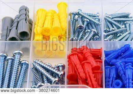 Set Of Colorful Dowel, Screw, Fastener. A Box With Dowel, Bolt And Screw. Set Of Building Tools.