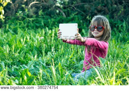 Little girl while taking a selfie in the green grass.