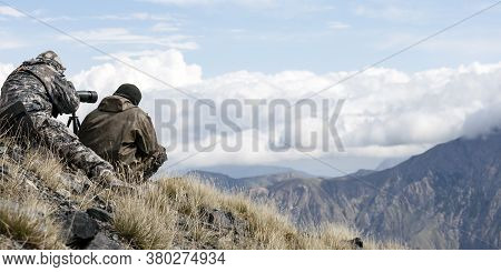 Hunters Watch The Animals On The Opposite Mountain Slope With A Telescope. Two Men In Camouflage Dis