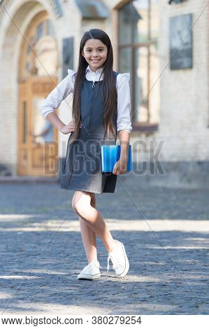 Going Back To School. Happy Child Back To School. Little Kid Hold Book Wearing Uniform. Formal Educa