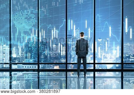 Businessman Standing In Office With Glowing Chart Hologram. Trade And Stats Concept. Double Exposure