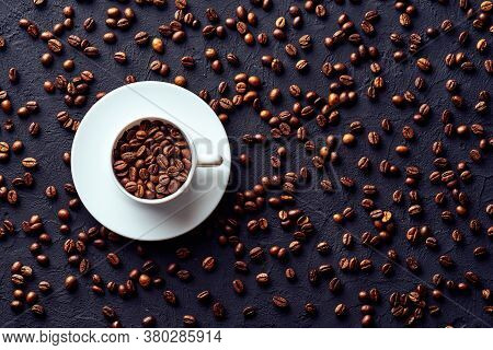 Top View Of Roasted Whole Coffee Beans In White Porcelain Cup On Saucer On Gray Background