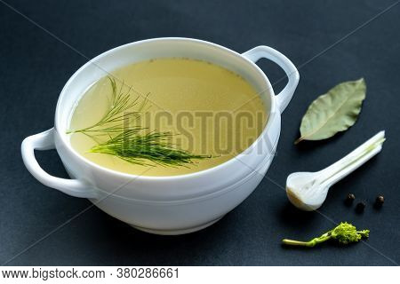 Homemade Broth Of Meat Bones In A Tureen, Vegetables And Seasonings, On A Black Background. Healthy