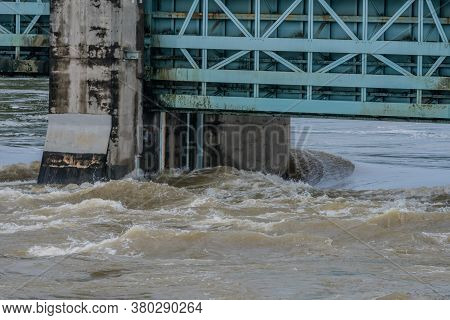 Closeup Of Dam With Water Surging Through Open Floodgates After Torrential Monsoon Rains