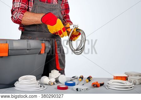 Electrician Engineer Works With Electric Cable Wires Of House. Electrical Equipment. Copy Space.