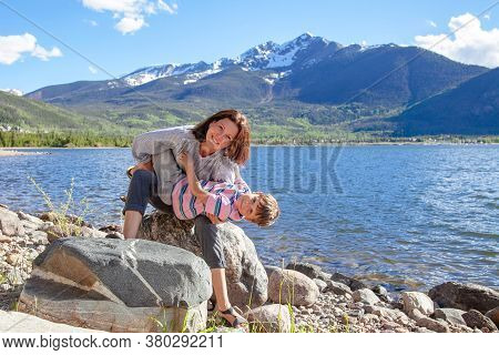 Young Tourist Mother Hugging Her Son Near The Lake With A Beautiful View Of The Mountains On The Bac
