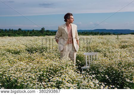 Tall Handsome Man Standing In Camomile Flowers Field